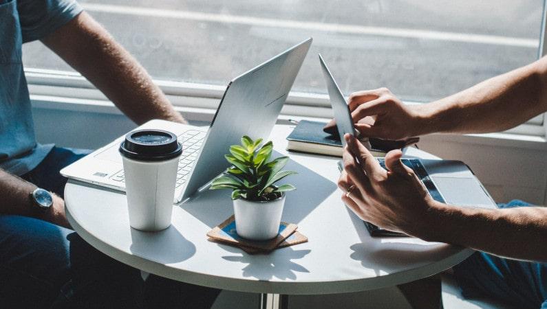dos personas laptops café